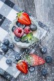 Yogur natural fresco y sano con las bayas en la tabla de madera Imagenes de archivo