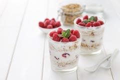 Yogur sano del desayuno con el granola y las frambuesas en vidrios en la tabla de madera blanca Imagenes de archivo