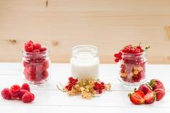 yogur y baya en los tarros de cristal en la tabla blanca Fotos de archivo