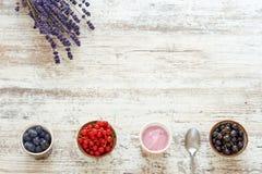 Yogur y bayas en una tabla de madera Foto de archivo
