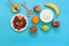 Yogur y frutas, bayas, nueces, miel como ingredientes Imagenes de archivo