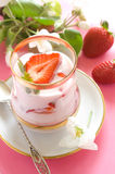 Yogurt. Strawberry yogurt with fresh strawberry in glass. On a pink background stock photography