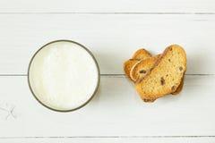 Yogurt acido in tazza di vetro e cracker con l'uva passa su una tavola bianca immagine stock libera da diritti