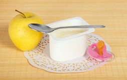 Yogurt, apple and pacifier. Yogurt, apple, a pacifier and a napkin on a bamboo cloth Stock Photo
