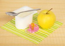 Yogurt, apple and pacifier Stock Images