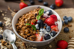 Yogurt with baked granola and berries in small bowl Stock Image