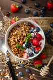 Yogurt with baked granola and berries in small bowl Royalty Free Stock Photo