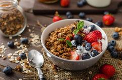 Yogurt with baked granola and berries in small bowl Royalty Free Stock Images