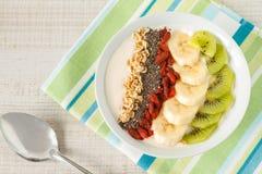Yogurt with banana, kiwi, chia seeds,goji berries and oats Royalty Free Stock Photo