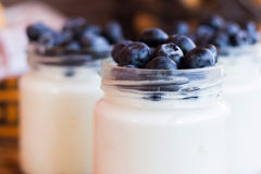 Yogurt with berries in a glass jar. Homemade yogurt with blueberries in a glass jar Stock Image