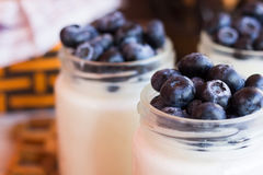 Yogurt with berries in a glass jar. Homemade yogurt with blueberries in a glass jar Royalty Free Stock Image