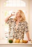 Yogurt bevente della donna in cucina Fotografie Stock