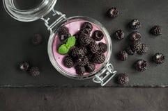 Yogurt with black raspberry or blackberry in glass jar. On black slate board Stock Photos