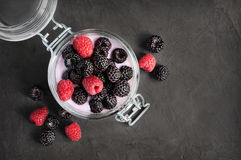 Yogurt with black and red raspberry in glass jar Royalty Free Stock Photography