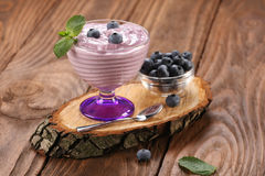 Yogurt with blueberries in a glass bowl and blueberries in a gla Royalty Free Stock Photos