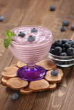Yogurt with blueberries in a glass bowl and blueberries in a gla Stock Photos