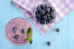 Yogurt with blueberries in a glass bowl and blueberries in a glass Royalty Free Stock Photo