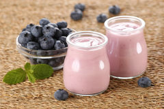 Yogurt with blueberries in a glass jar and blueberries in a glas Royalty Free Stock Photos