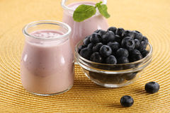 Yogurt with blueberries in a glass jar and blueberries in a glas Stock Photos