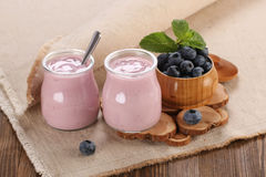 Yogurt with blueberries in a glass jar and blueberries in a wood Royalty Free Stock Photo