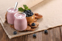 Yogurt with blueberries in a glass jar and blueberries in a wood Stock Photography