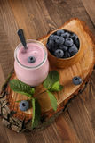 Yogurt with blueberries in a glass jar and blueberries in a wood Stock Image