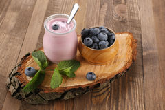 Yogurt with blueberries in a glass jar and blueberries in a wood Royalty Free Stock Image