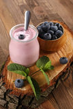 Yogurt with blueberries in a glass jar and blueberries in a wood Royalty Free Stock Photos