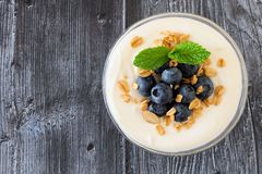 Yogurt with blueberries, granola, above view on rustic dark wood Royalty Free Stock Photography