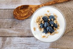 Yogurt with blueberries, granola, above view on rustic wood Royalty Free Stock Photography