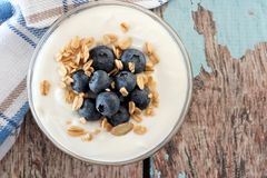 Yogurt with blueberries, granola, close up over a wooden background Royalty Free Stock Image