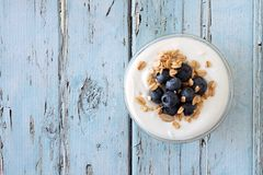 Yogurt with blueberries, granola, top view on rustic blue wood Stock Photos