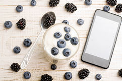Yogurt with blueberries, a smartphone, a teaspoon of blackberry on the white wooden background, top view Royalty Free Stock Images