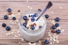 Yogurt with blueberry and cereal of glass in a jar on a wooden t. Able. Light morning diet breakfast royalty free stock image