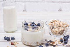 Yogurt with blueberry and cereal of glass in a jar on a wooden t. Able. Light morning diet breakfast stock image