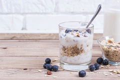 Yogurt with blueberry and cereal of glass in a jar on a wooden t. Able. Light morning diet breakfast royalty free stock photos