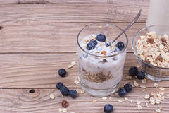 Yogurt with blueberry and cereal of glass in a jar on a wooden t. Able. Light morning diet breakfast royalty free stock images