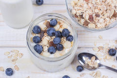 Yogurt with blueberry and cereal of glass in a jar on a wooden t. Able. Light morning diet breakfast stock images