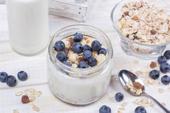 Yogurt with blueberry and cereal of glass in a jar on a wooden t. Able. Light morning diet breakfast royalty free stock photography