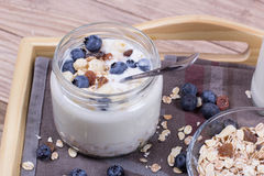 Yogurt with blueberry and cereal of glass in a jar on a wooden t. Ray. Light morning diet breakfast stock photos