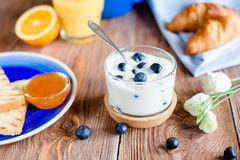 Yogurt with blueberry in a glass. Breakfast with yoghurt with blueberry, toasts with jam and croissants on a blue plate served on wooden table stock photos