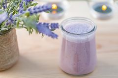 Yogurt with blueberry in jars in an orchard in summertime. Evening light. Bouquet of flowers. stock photo
