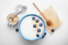 Yogurt with blueberry and oat flakes in dish. On white background stock photo