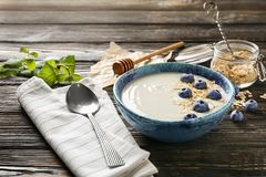 Yogurt with blueberry and oat flakes in dish. On wooden table stock image