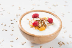 Yogurt bowl with fresh raspberry, apricot and granola. Yogurt bowl with fresh raspberries, apricots and muesli in a wooden bowl on white background. Meal for Royalty Free Stock Image