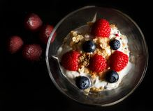 Yogurt bowl with raspberries and oat flakes. Yogurt bowl with oat flakes, blueberries and raspberries on black background. Healthy breakfast concept. Dark moody Stock Images