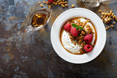 Yogurt bowl with raspberry and maple syrup. Yogurt bowl with granola, raspberry and maple syrup overhead shot Stock Photos
