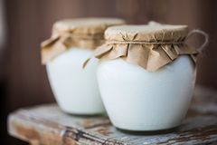 Yogurt casalingo del latte in barattoli fotografia stock