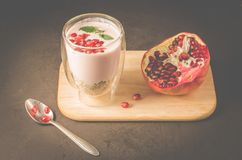 Yogurt. Yogurt with cereals, garnet and mint in glass and pomegranate fruit on a wooden tray. Dark backgtound table. Sweet dessert royalty free stock photos