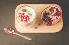 Yogurt. Yogurt with cereals, garnet and mint in glass and pomegranate fruit on a wooden tray. Dark backgtound table. Top view. stock image